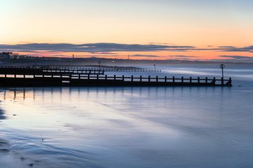 Long exposure of beach with groynes at twilight. Aberdeen, Scotland, UK.