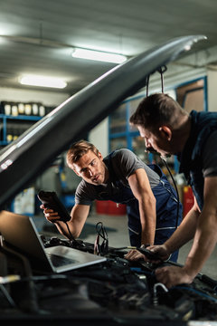 Auto mechanics using diagnostic tools while repairing car in a workshop.