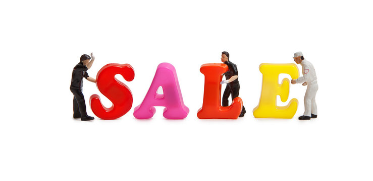 """Little men with a word of plastic letters """"Sale"""". Isolated on white background."""