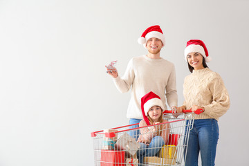 Family with shopping cart full of Christmas gifts on light background