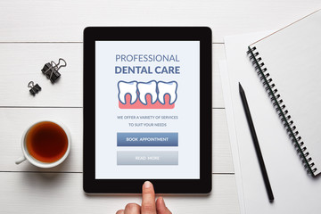 Dental care concept on tablet screen with office objects on white wooden table. Top view