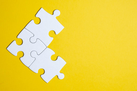 Three pieces of a puzzle united among themselves on a yellow background. Teamwork concept.