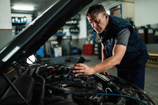 Auto mechanic checking engine under the hood at repair shop.