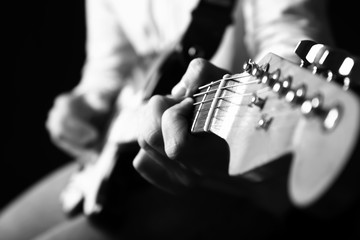 Black and white photo of man with guitar, closeup