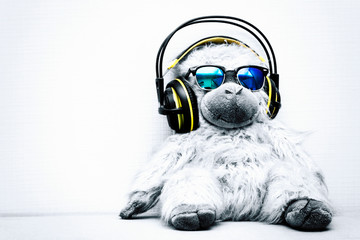 Concept of a dance monkey listening to music on headphones and wearing sunglasses