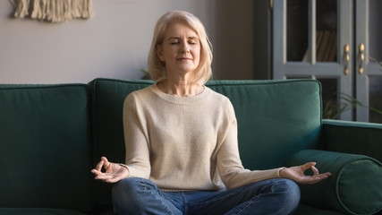 Serene elderly woman sit in lotus position meditating at home