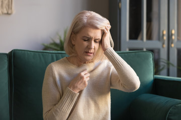 Mature woman sit on couch touches head feels unhealthy