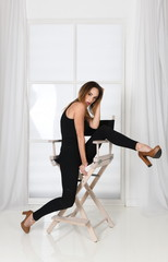 Young woman in tight black tank top, leggings and high heels sitting on a chair in provocative sexy pose