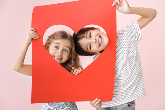 Cute little children holding paper sheet with hole in shape of heart on color background. Valentines Day celebration