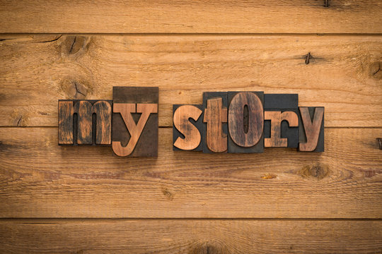 My story, phrase written with vintage letterpress printing blocks on rustic wood background