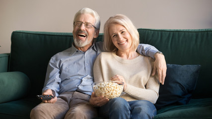 Laughing mature spouses sitting on couch watching comedy at home
