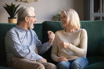 Cheerful elderly spouses sitting on couch chatting feel happy