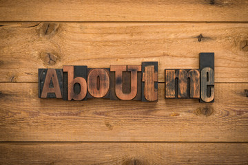 About me, phrase written with vintage letterpress printing blocks on rustic wood background