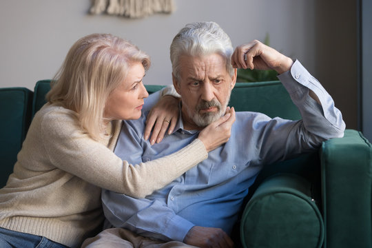 Middle aged wife comforting upset grey-haired husband