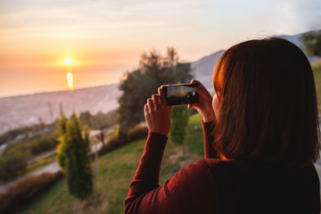 Traveler woman use mobile phone take a photo of beautiful of sunset nature at top of mountain sea view. Deep red sun rays.
