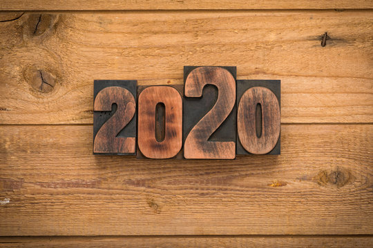 Year 2020 written with vintage letterpress printing blocks on rustic wood background