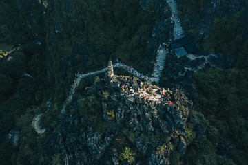 Aerial drone sunset photo of the top of Hang Mua mountains with the famous dragon statues and pagoda