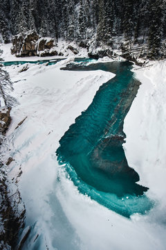 Partially frozen river with blue water in winter