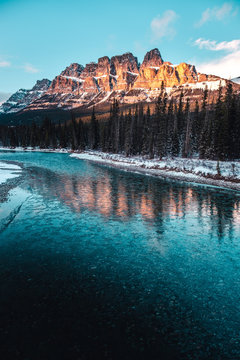 Reflection of Castle Mountain on icy river at sunset