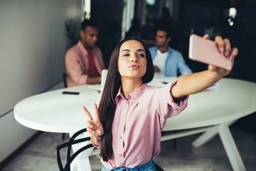 Positive female showing v-sign for taking funny pictures using application for blogging on smartphone gadget, Caucasian hipster girl with duck face clicking selfie photos via modern mobile phone