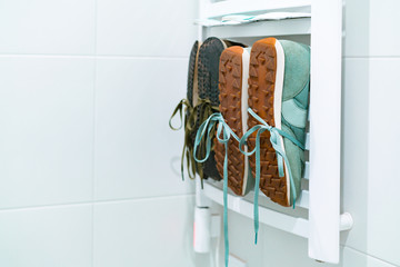 Two pairs of sneakers tied to heated towel rail to dry. Washing. Cleaning up. Purely. Idea to dry your shoes. Footwear. Quick dry. Bathroom. White