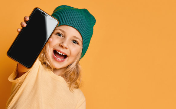 Smiling screaming little girl kid in green modern winter hat showing blank screen of new popular mobile phone gadget