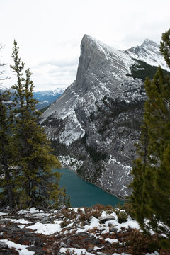 Rocky mountain above lake with dusting of snow