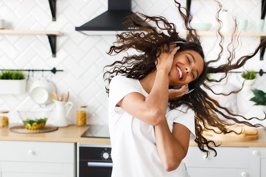 Happy african girl twirls her hair and listens to music via headphones in the kitchen