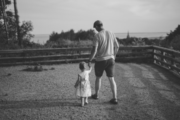 Happy loving family. Father and his daughter child girl playing and hugging outdoors. Cute little girl hugs daddy. Concept of Father's day. Authentic image