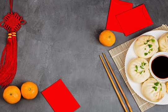 Chinese New Year decoration with dumplings, tangerines, soy sauce, chopsticks, red envelopes on gray concrete background. Happy Chinese new year 2020 festival