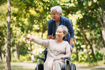 asian senior couple relaxing in park