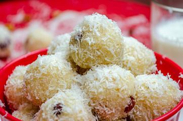 Close-up of coconut rava ladoos in a bowl.