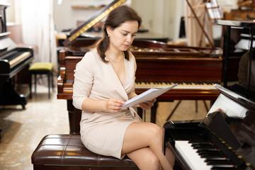 Spoed Foto op Canvas Muziekwinkel Female assistant or customer at piano music store