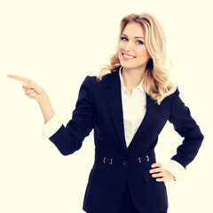 Businesswoman in confident style black suit, pointing at something, some product or blank copy space area for advertise slogan or text message. Caucasian blond model in business success concept.