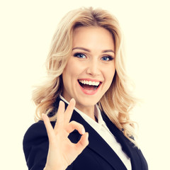 Happy smiling beautiful businesswoman in confident style black suit, showing okay hand sign gesture. Caucasian blond model in business success concept.