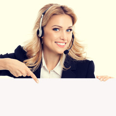 Call center. Customer support phone operator in confident style black suit and headset showing signboard with copy space area for text or advertise slogan. Caucasian model in business success concept.