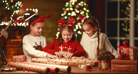 happy funny children girls pack Christmas gifts at evening in home.