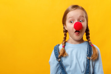 Funny child clown with a red nose. Cheerful little girl on a yellow background. April 1st Fool's Day. Copy space