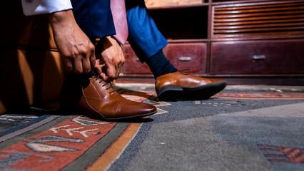 novio vistiendo su calzado antes de su boda Wall mural