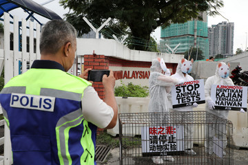 A police officer takes a picture of activists from PETA (People for the Ethical Treatment of Animals), dressed as rats, protesting against what they say is Ajinomoto's use of animal testing outside the company's headquarters in Kuala Lumpur