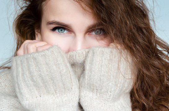 Winter portrait of a beautiful curly woman with blue eyes in a warm sweater with a pierced nose.