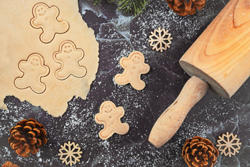 Flat lay concept for baking Christmas cookies with rolled out cookie dough, cookies in the shape of happy gingerbread men, rolling pin and seasonal fir branches on dark marble background