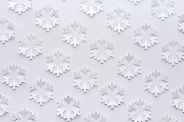 White winter background made from snowflakes cut out on a sheet of paper.