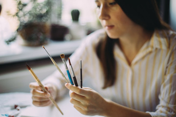 girl artist holds brushes in her hands. creation. drawing. art