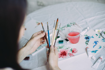 girl artist holds brushes in her hands. creation