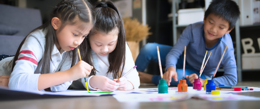 Asian family with cute kids painting art in living room at home