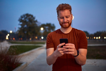Man using cellphone in urban park at night.