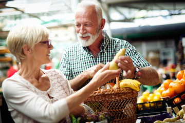 Mature couple shopping vegetables and fruits on the market. Healthy diet.