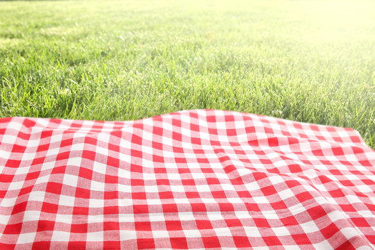 Picnic cloth on green grass background empty space.