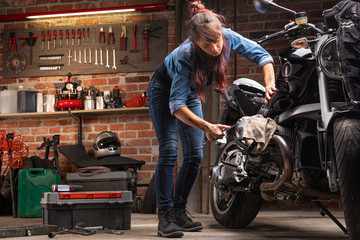 Woman mechanic working on a vintage motorbike